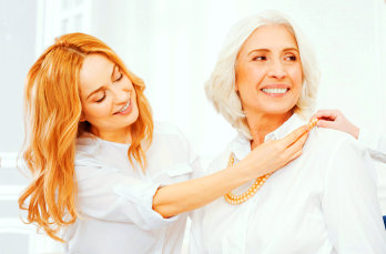 adult woman assisting senior woman in dressing