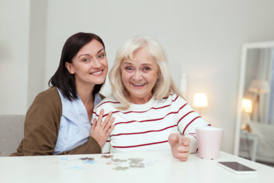 Enthusiastic elder woman and caregiver looking at camera while gathering puzzle