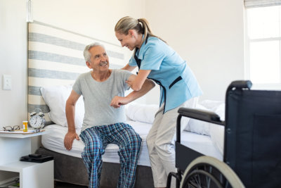 Smiling nurse assisting senior man getting up from bed.