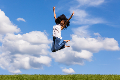 Outdoor portrait of a smiling teenage black girl jumping over a blue sky
